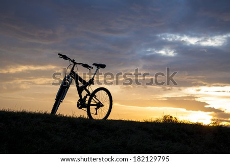 Evening recreation with bicycle with sunset and dramatic sky - stock photo