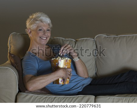 Evening scene of mature woman lounging on sofa watching TV and eating popcorn - stock photo