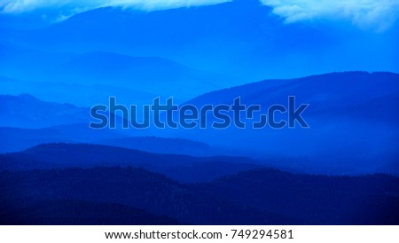 evening scene with blue misty valley in mountains