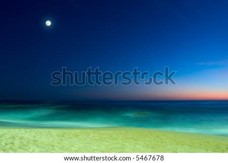 evening seascape with sandy beach, calm ocean and full moon on blue sunset sky - stock photo