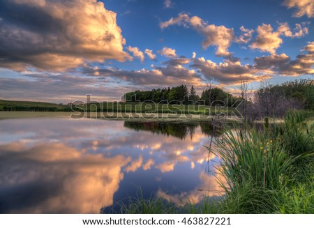 Evening Sky: The clouds absorb the last minutes of light and cast a beautiful reflection onto a small pond in Saskatchewan