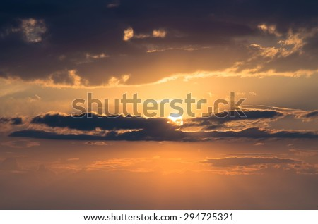 evening sun behind the clouds - stock photo