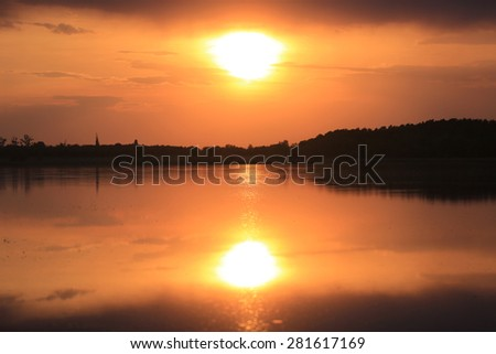 Evening sun over lake surface - stock photo