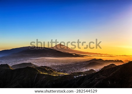 Evening sunset in mountains and blue sky with fog or haze and Teide volcano on background in Tenerife Canary island, Spain at spring or summer