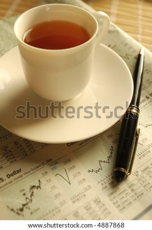 Evening tea over business newspaper - stock photo