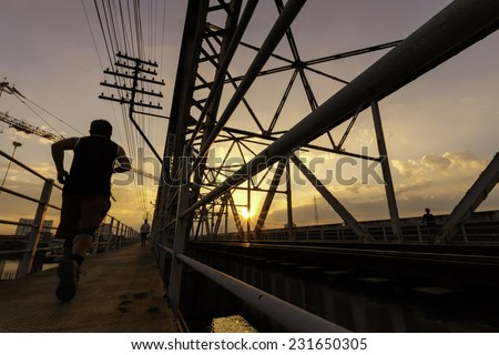 evening time view of a man running along situate old steel bridge structure and railway - stock photo