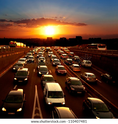 Evening traffic. The city lights. Car traffic against the sunset background.