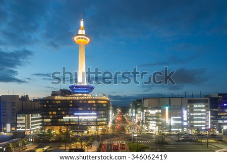 Evening twilight aerial view of lighted Kyoto Tower, downtown buildings and trailing traffic lights at dusk during blue hour in the ancient city of Kyoto, Japan. Horizontal copy space