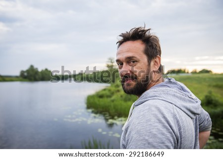 Evening twilight. Portrait of a mature man in the river landscape background. - stock photo