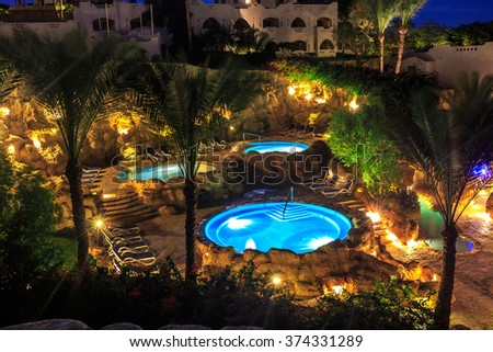 Evening view for luxury swimming pools in night illumination - stock photo
