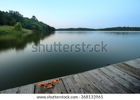 Evening view of a lake with a dock in the foreground - stock photo