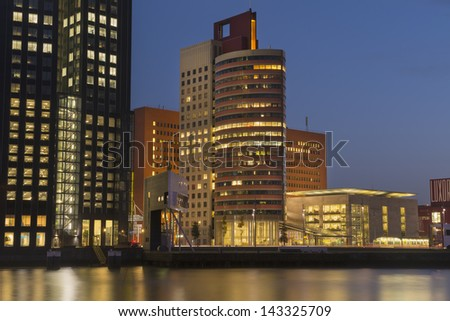 Evening view of illuminated modern office buildings. Rotterdam, The Netherlands. - stock photo