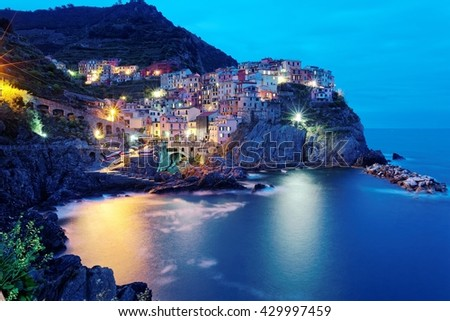 Evening view of Manarola on vertical cliffs by the rocky coast with beautiful lights reflecting on sea water, an amazing village in Cinque Terre National Park, Liguria, Italy, Europe (Long Exposure) - stock photo