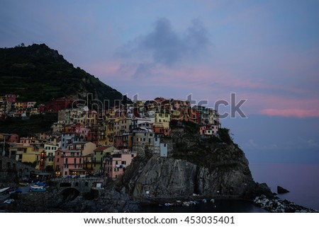 Evening view of Manarola on vertical cliffs by the rocky coast with beautiful lights reflecting on sea water, an amazing village in Cinque Terre National Park, Liguria, Italy, Europe - stock photo