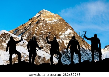 Evening view of Mount Everest and silhouette of climbers with ice axe in hand, extreme sport in Nepal, Khumbu valley, Solukhumbu, trek to Everest base camp, Sagarmatha national park - stock photo