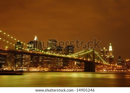 Evening view of the Brooklyn Bridge with Waterfall under and NYC skyline behind