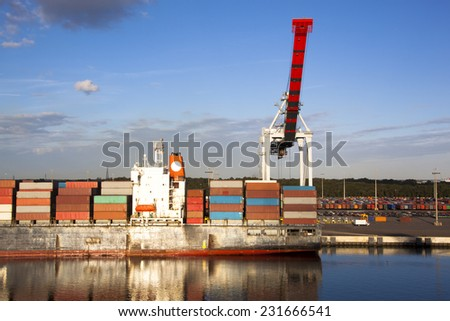 Evening view of the red crane and a cargo ship in Jacksonville city port (Florida). - stock photo