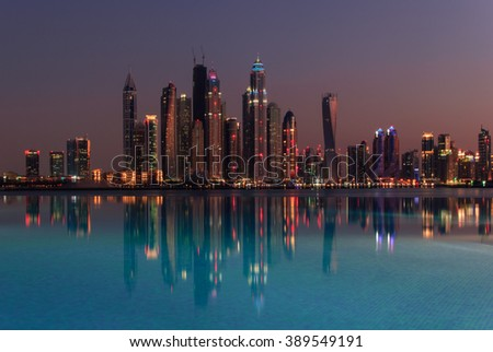 Evening view of the skyscrapers of Dubai Marina and their reflection in the pool. - stock photo