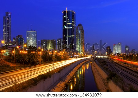 Evening view on illuminated modern office buildings, Azrieli towers  and light traces on Ayalon highway in downtown of Tel Aviv, Israel.. - stock photo