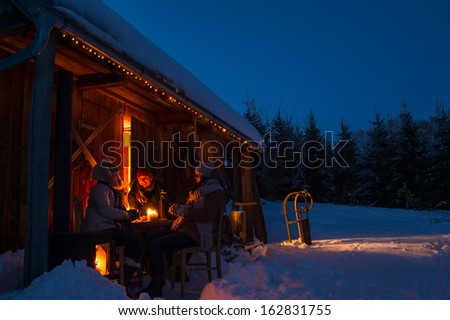 Evening winter cottage friends enjoy hot drinks in snow countryside - stock photo
