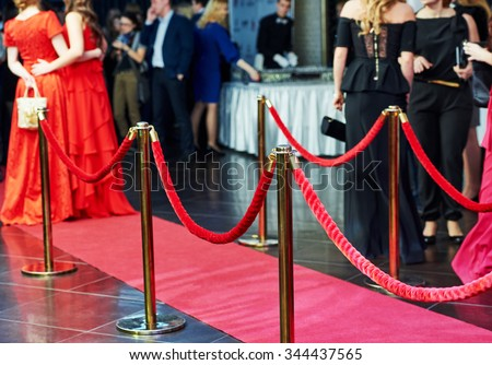 event party. red carpet entrance with golden stanchions and ropes. guests in the background  - stock photo
