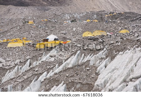 Everest Base Camp. Cluster of yellow tents on the rubble strewn Khumbu glacier at the base of Mount Everest, Nepal - stock photo