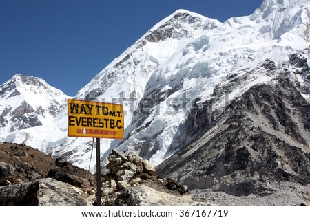 Everest Base Camp sign with snow capped mountain and blue sky, Himalayas, Nepal