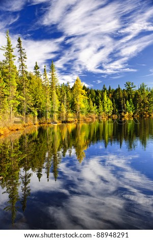 Evergreen forest and sky reflecting in calm lake at Algonquin Park, Canada - stock photo