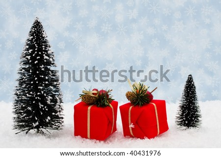 Evergreen trees sitting with presents with a blue snowflake background, Christmas gifts