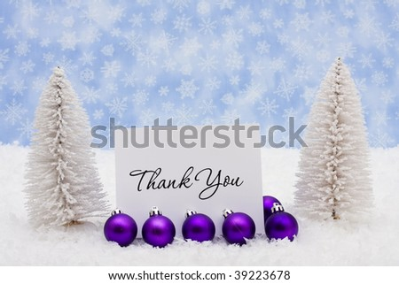 Evergreen trees sitting with purple glass Christmas balls and a thank you card on snow with a blue snowflake background - stock photo