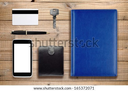 Everyday accessories and objects on wooden background - stock photo