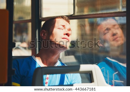 Everyday life and commuting to work by public transportation. Handsome young man is traveling by tram (bus). Tired man in hot day. Prague, Czech Republic - stock photo