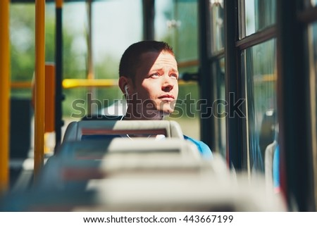Everyday life and commuting to work by public transportation. Handsome young man is traveling by tram (bus).  - stock photo