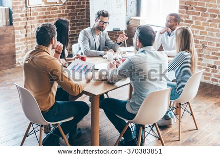 Everyday meeting. Group of six young people discuss something and gesturing while sitting at the table in office - stock photo