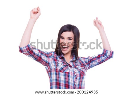 Everyday winner. Happy young smiling woman keeping arms raised and looking at camera while standing isolated on white - stock photo