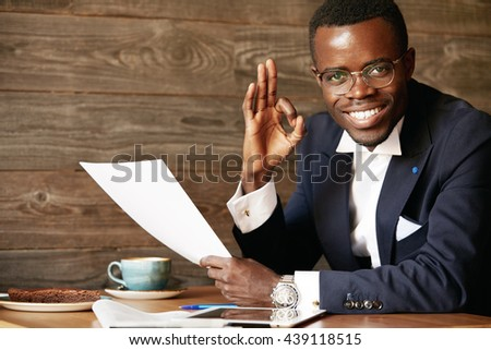 Everything is perfect! Portrait of happy cheerful African American executive officer in glasses looking at the camera with confident pleased expression, gesturing 'OK' sign, holding business papers - stock photo