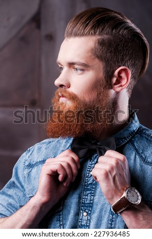 Everything must perfect. Profile portrait of handsome young bearded man adjusting his bow tie and looking away - stock photo