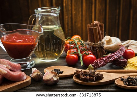 everything on wood table for the preparation of acute Italian sauce (tomato garlic spices olive oil) - stock photo