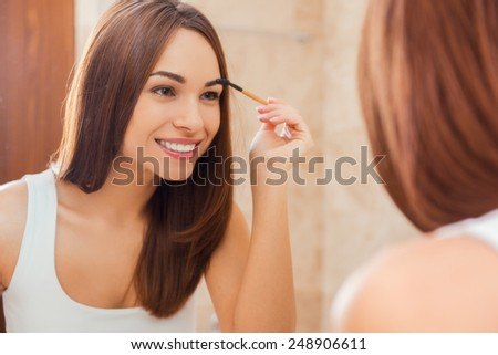 Everything should be perfect. Attractive young woman doing make-up while looking at the mirror and smiling - stock photo