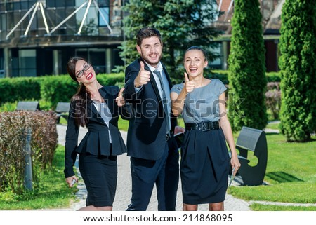 Everything will be fine. Three successful business people in formal clothes standing on the street to discuss business and keep computers in their hands. Young businessman smiling and raise thumbs up