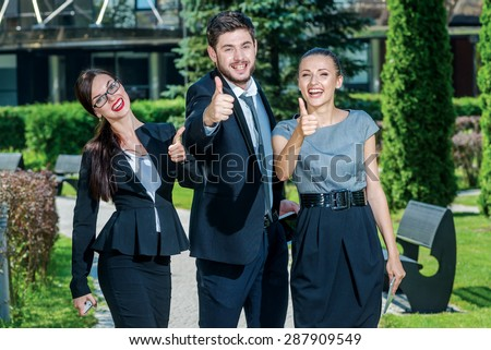 Everything will be fine. Three successful business people in formal clothes standing on the street to discuss business and keep computers in their hands. Young businessman smiling and raise thumbs up - stock photo