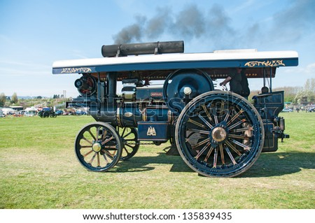 EVESHAM,WORCESTER,ENGLAND - APRIL 13: A vintage steam traction engine with its owners on display in the show ring at a country fair on April 13,2009 in Evesham,England - stock photo