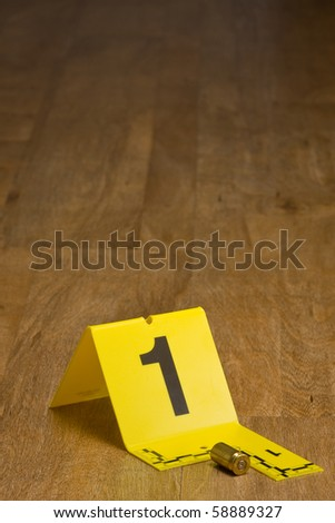 Evidence marker with bullet casing on wooden floor with copy space