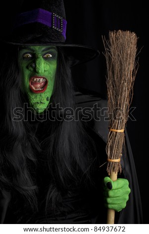 Evil and her broomstick, black background - stock photo