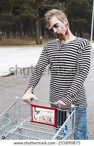 Evil bleeding zombie carring a shopping wagon - stock photo