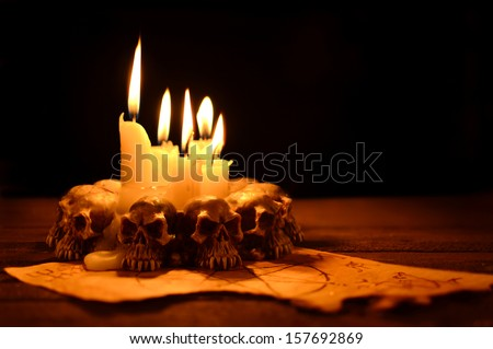 Evil candles on wooden background in the darkness - stock photo
