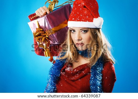 Evil Christmas girl with a gift box against blue background - stock photo