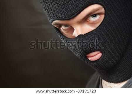 Evil criminal in a mask looking at the viewer; copy space on the left. - stock photo