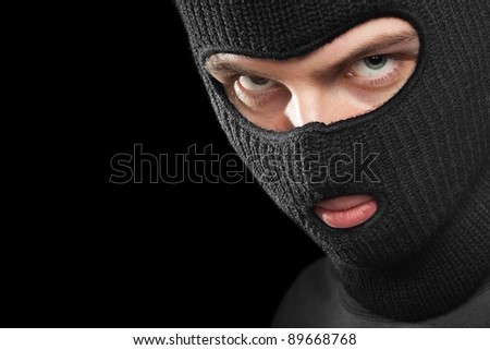 Evil criminal in a mask looking at the viewer; isolated on black background, copy space on the left. - stock photo