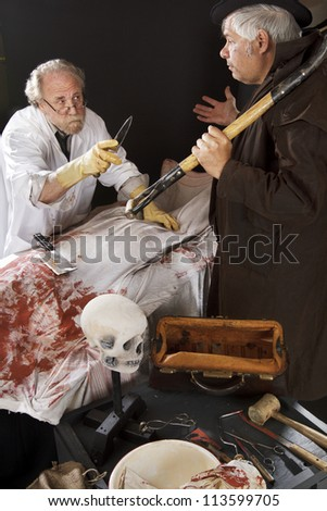 Evil doctor gestures menacingly with knife at grave robber over bloody corpse. Stage effect, isolated on black background, spot lighting. - stock photo